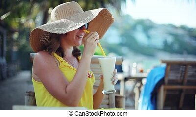 Young elegant happy woman wearing hat and sunglasses on holiday, sitting in a cafe with scenic views of the sea drinks cocktail. 1920x1080