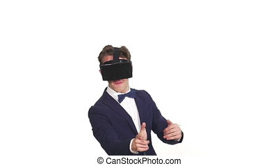 Young elegant man in a studio with white background playing a virtual reality game