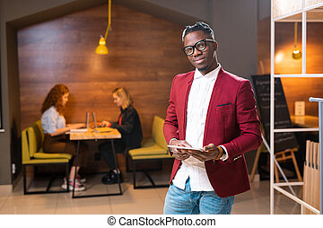 Young elegant man of African ethnicity in smart casualwear using digital tablet