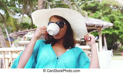 Young elegant pretty woman wearing hat and sunglasses on holiday, sitting in beach cafe with scenic views of the sea and palm trees drinks coffee has a breakfast. slow motion. 3840x2160