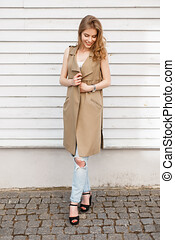 Young elegant woman in a beige vest in a white T-shirt in stylish blue ripped jeans in black sandals with a black handbag is standing near a wooden white vintage wall. Cute european girl on a walk