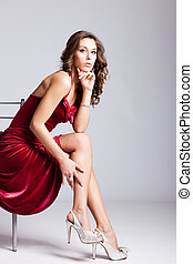 young elegant woman in red dress sit on chair, studio shot