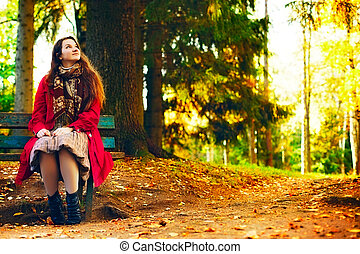Young elegant woman  sitting on bench