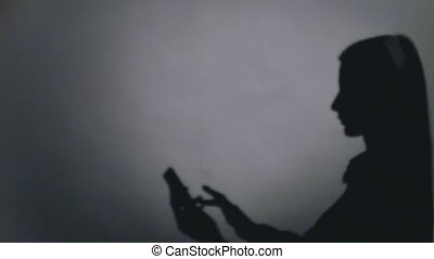 Young elegant woman talking on mobile phone against black background with shadow