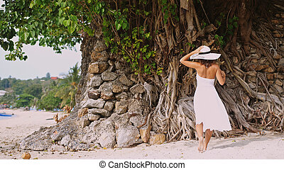 Young elegant woman with long hair in white drees and hat walking on tropical beach