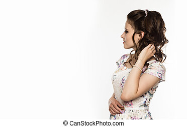young elegant woman with professional hairstyle poses on a white background. free space for your text