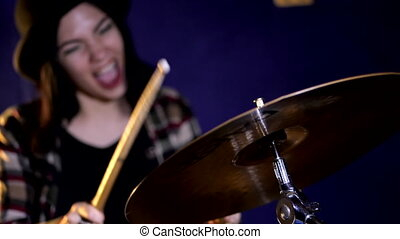 Young Emotional Rock girl percussion drummer performing with drums, slow motion. Attractive young woman plays the drums.