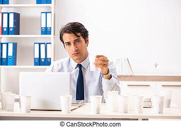 Young employee addicted to coffee