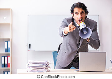 Young employee boss with megaphone in the office