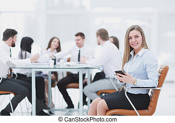 young employee with a smartphone on the background of business team