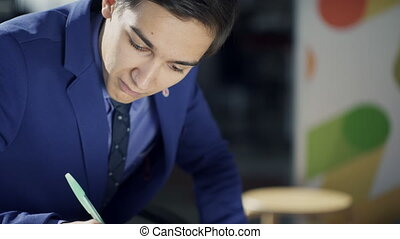 Young employee writes with pen sitting at table indoors. Man dressed in stylish business suit an shirt with black tie