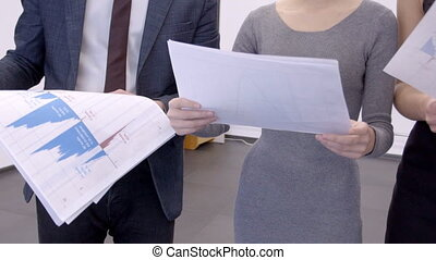Young employees are studying paper blueprint, standing in modern office.