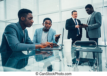 young employees discussing online news in the workplace.