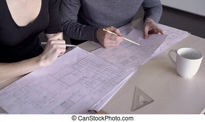 Young employees work on blueprint at table in modern office.