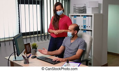 Employees with protection mask working in new normal office during covid-19 pandemic. Team in modern company workspace discussing looking at computer pointing at desktop analyzing clients list