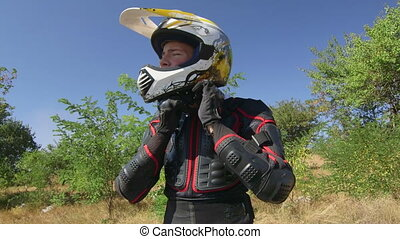 Young enduro racer dressing motorcycle protective gear and riding away