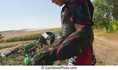 Young enduro racer dressing motorcycle protective gear beside his dirt bike