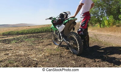 Young enduro racer stands next to his dirt bike looking afar