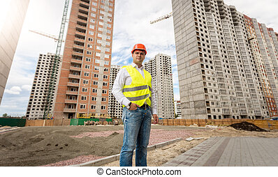 Young engineer in hardhat and safety vest posing against buildings under construction