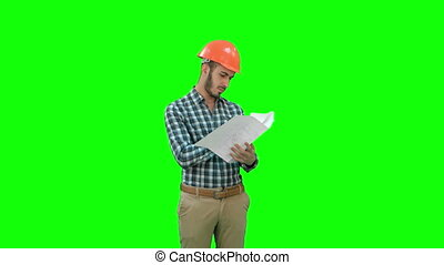 Young engineer in helmet checking construction plan on a Green Screen, Chroma Key.
