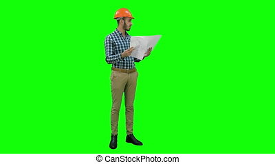 Young engineer in helmet checking construction drawings on a Green Screen, Chroma Key.