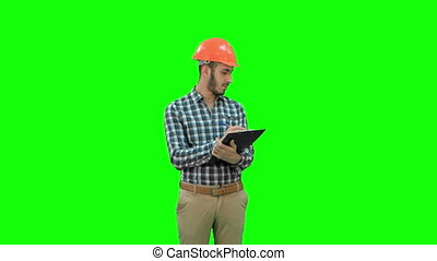 Young engineer in helmet inspecting construction site on a Green Screen, Chroma Key.