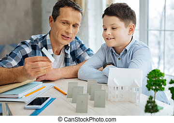 Young engineer showing solar panel model to his son