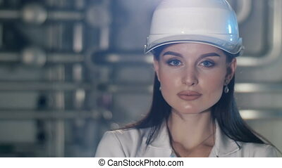 Portrait of a beutiful woman at hard hat at the factory