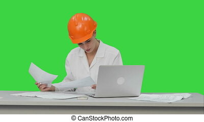 Young engineer woman reading technical drawings on a Green Screen, Chroma Key.
