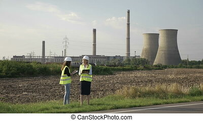 Young engineer women with helmet holding map and using ...