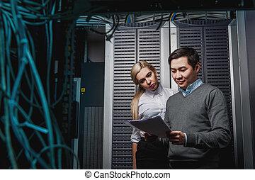 Young engineers businessmen in server room