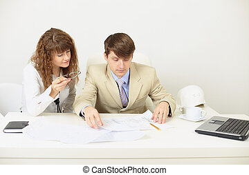 Young engineers plan work sitting at a table