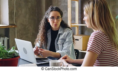Young enterpreneur is talking to her partner in modern...