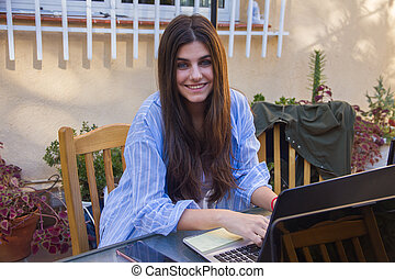 Young enterprising girl working with laptop on the terrace of her house.