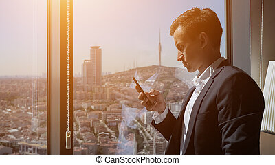 Young entrepreneur in office suit is browsing phone near the window with panoramic city view.