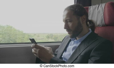 Young entrepreneur man commuter on train sitting next the...