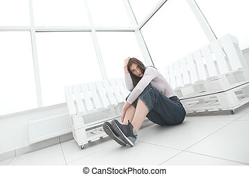 young entrepreneur sitting on the floor in her new office
