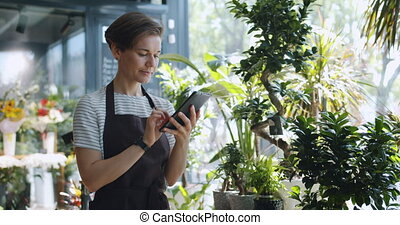Young entrepreneur touching tablet screen looking at flowers...