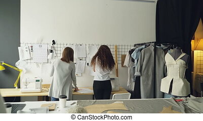 Young entrepreneurs clothing designers standing in front of wall with hanging sketches, discussing drawings and placing images with clips. Creative team working together concept.