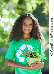 Young environmental activist smiling at the camera holding a...