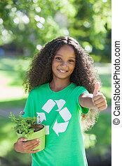 Young environmental activist smiling at the camera holding a...