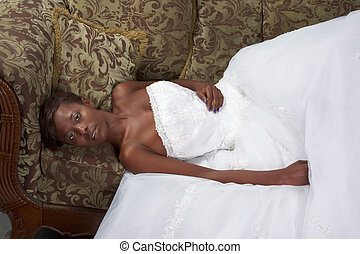 Young ethnic black woman bride in wedding dress on couch