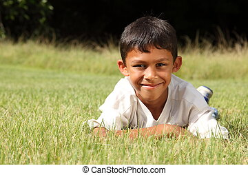 Young ethnic boy on grass in park