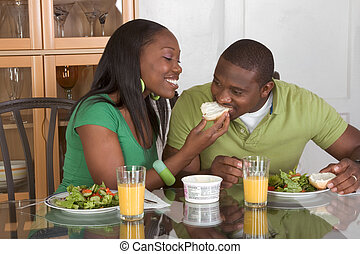 Young ethnic couple by table eating breakfast
