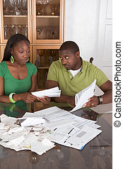 Young ethnic couple by table overwhelmed by bills - Young ...