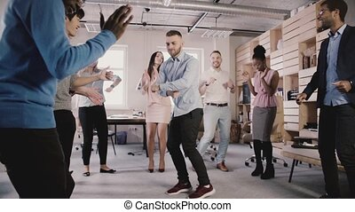 Young European businessman dancing in circle with colleagues...