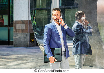 Young European Businessman talking on cell phone by mirror