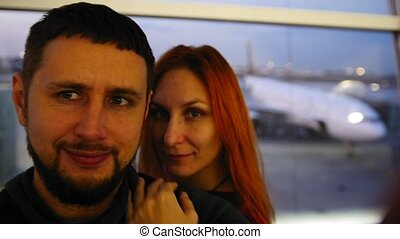 Young european couple Man and Woman make Selfie at Departure Lounge at the Airport in front of airplane