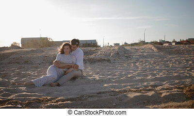 Young european couple sit on the sand