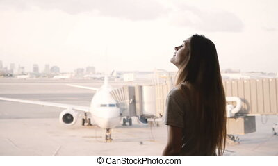 Young European girl talks on smartphone and smiles, ends call at airport terminal window, airplane in the background.